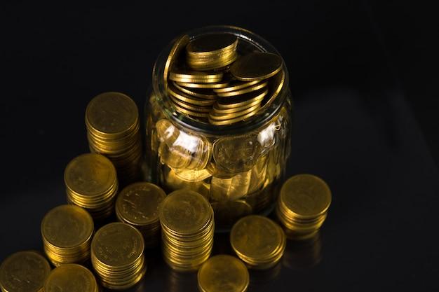 Moedas empilha dinheiro na jarra de vidro