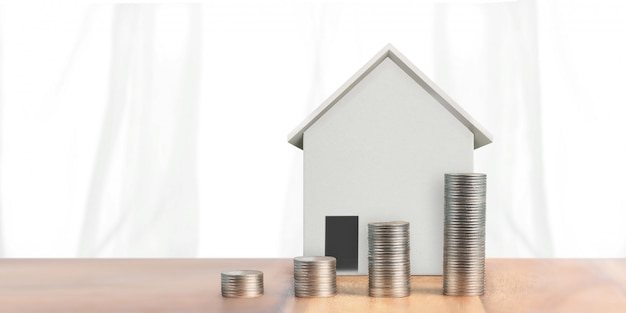 Moedas empilhadas e modelo de casa