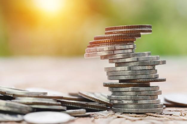 Moedas empilhadas na mesa desfocam o fundo da natureza, economizando dinheiro para o futuro, o conceito de negócio de investimento.
