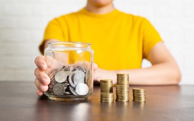 Moedas empilhadas salvar conceito, mulher segurando o frasco para guardar dinheiro