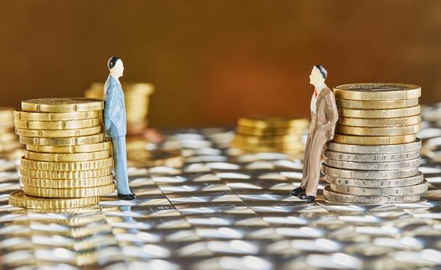 Moedas empilhadas umas sobre as outras com figuras de empresários em crise e frágil mercado