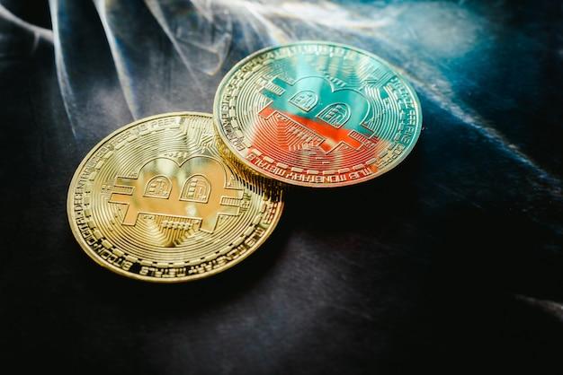 Moedas físicas de bitcoin iluminadas por raios claros com fundo escuro.