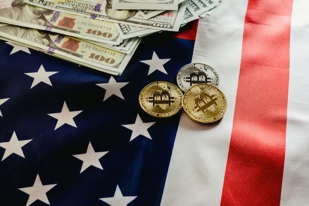 Moedas físicas de bitcoin no fundo da bandeira americana com dólares no fundo.