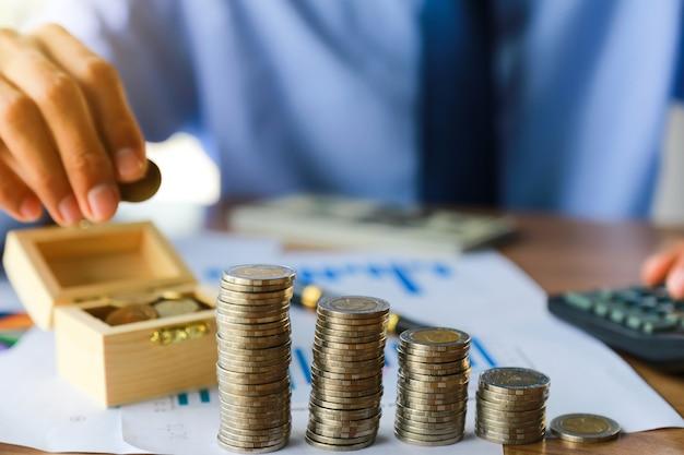 Moedas na mesa em seu escritório em finanças, investimento, poupança e conceito bancário.