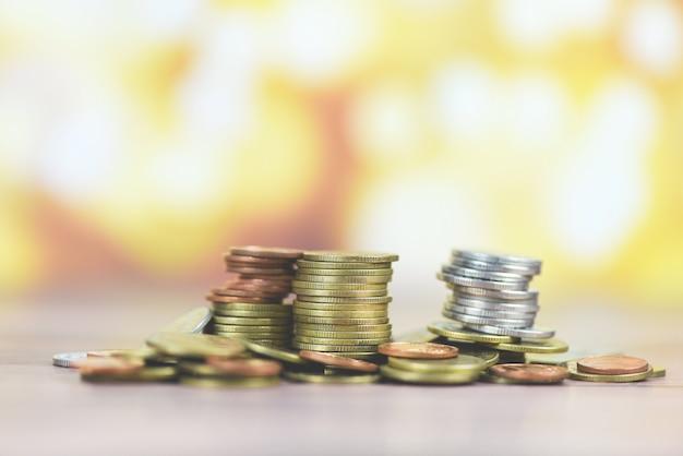 Moedas na mesa - pilha de moedas de ouro, moedas de prata e moedas de cobre no conceito financeiro de dinheiro de madeira