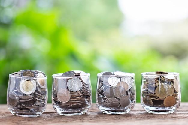 Moedas no frasco do dinheiro na prancha de madeira com fundo verde do borrão. conceito de poupança.