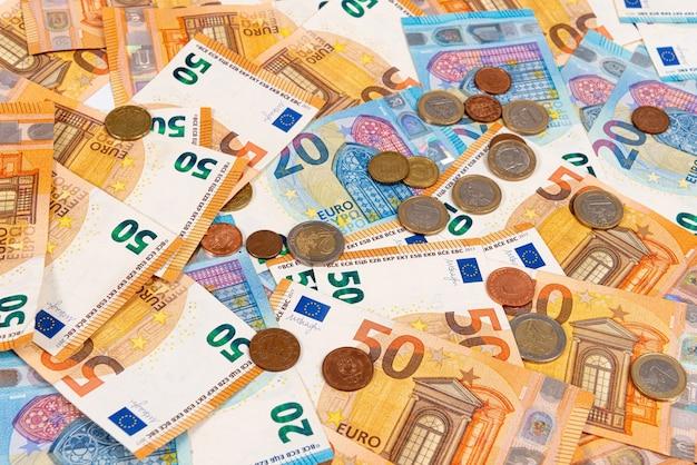 Moedas no fundo das notas de euro, notas de euro como parte do sistema econômico e comercial, close-up