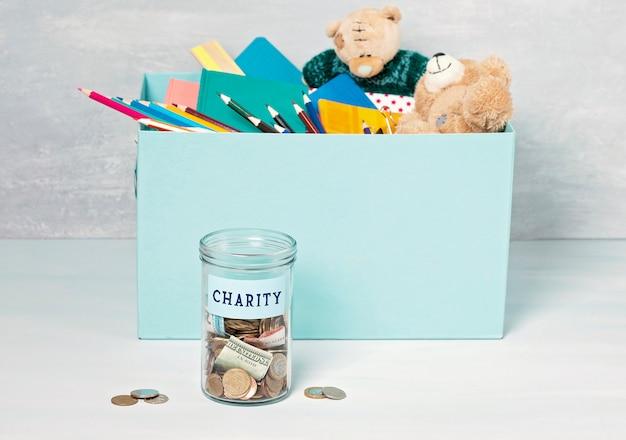 Moedas, notas em pote de dinheiro e caixa com doações