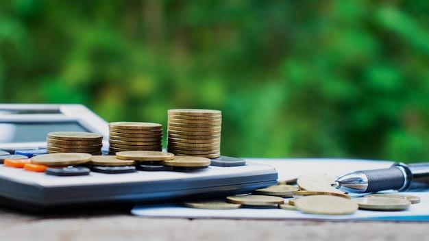 Moedas ou dinheiro em calculadoras, conceitos de contabilidade financeira e economizar dinheiro