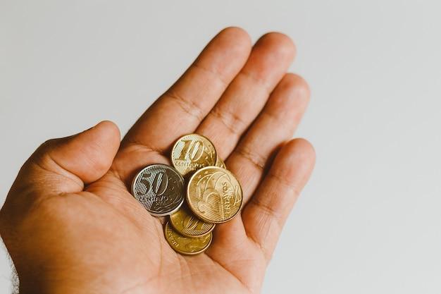 Moedas reais - dinheiro de brasil - mão do homem com centavos múltiplos - fundo branco.