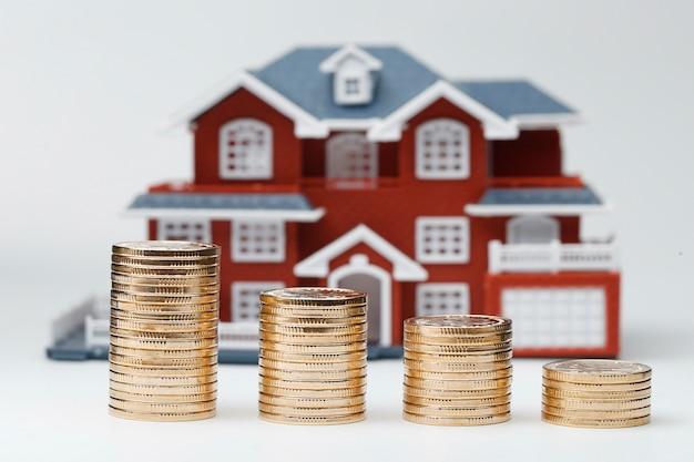 Moedas rmb empilhadas em frente ao modelo habitacional (preços das casas, compra de casas, imobiliário, conceito de hipoteca)