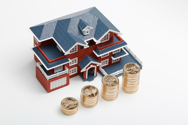 Moedas rmb empilhadas em frente ao modelo habitacional (preços das casas, compra de casas, imóveis, conceito de hipoteca)