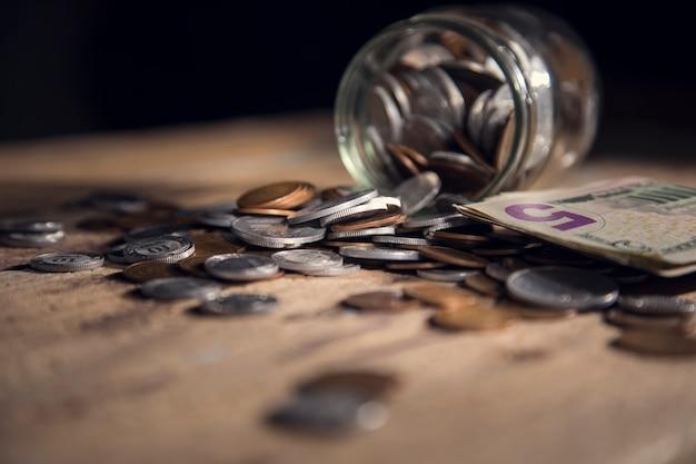 Moedas são derramadas de uma garrafa de vidro sobre uma mesa de madeira