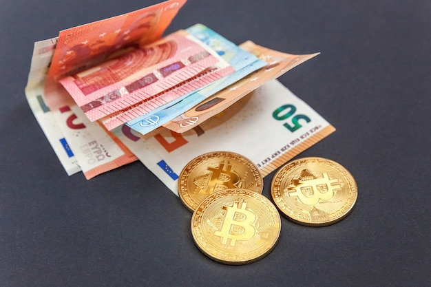 Moedas simbólicas de ouro de bitcoins nas notas de euro