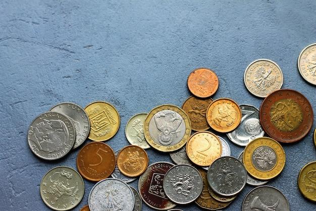 Moedas velhas de países diferentes em um fundo concreto cinzento.