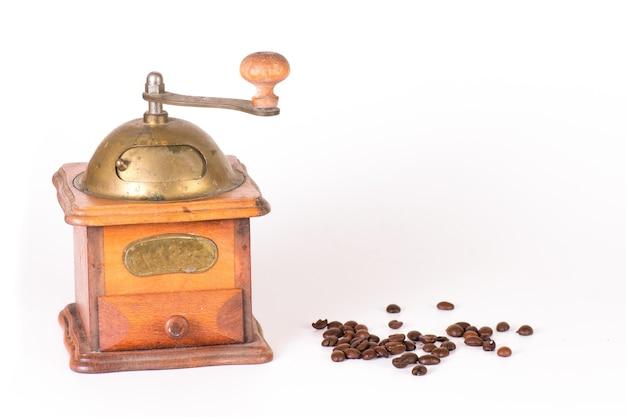 Moedor de café com alguns grãos espalhados em um branco