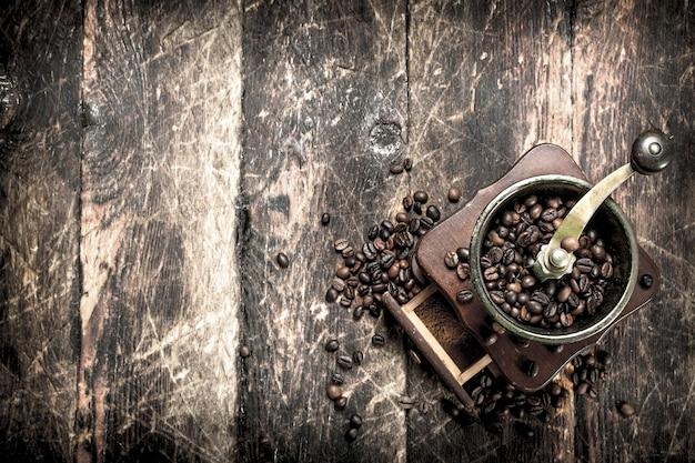 Moedor de café com grãos de café. sobre um fundo de madeira.