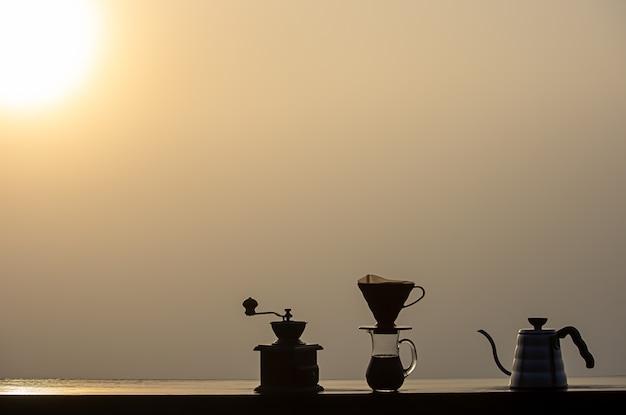 Moedor de café de madeira, jarros de vidro e silhuetas de chaleiras