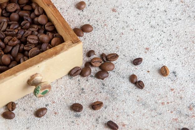 Moedor de café de madeira velho no fundo concreto.
