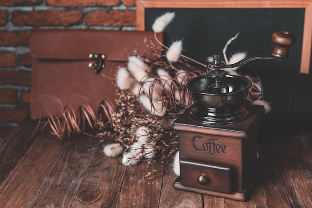 Moedor de café e café beens na decoração de serapilheira com flores secas e quadro-negro