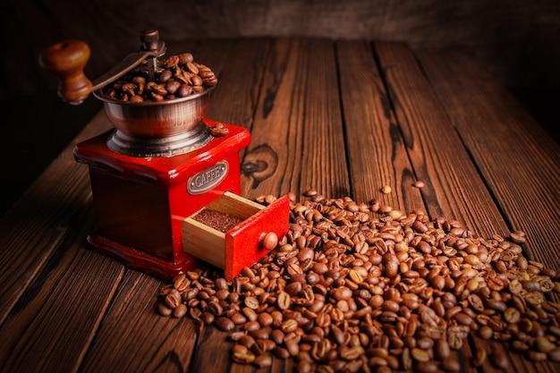 Moedor de café e café em superfície de madeira