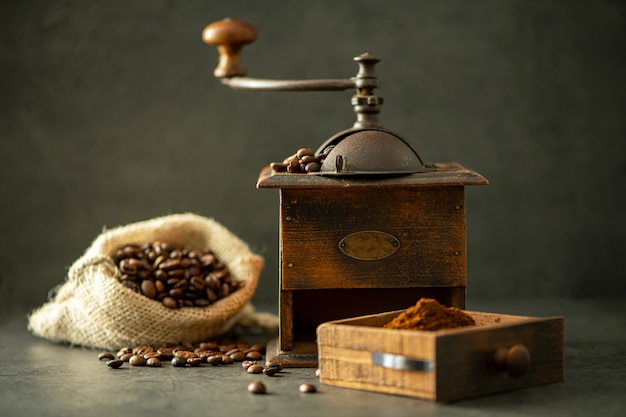 Moedor de café e feijão no fundo de madeira