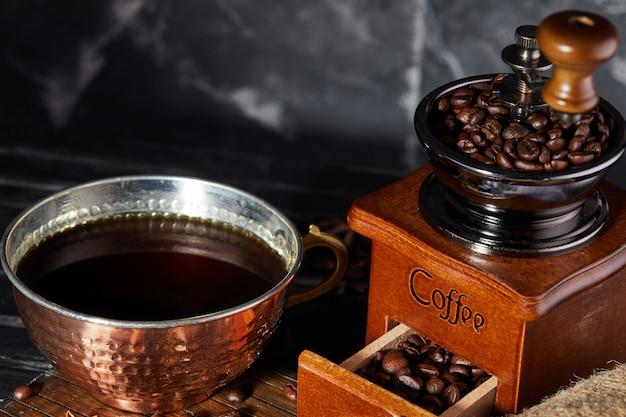 Moedor de café manual velho com grãos de café e uma xícara de café em um cinza. café