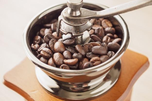 Moedor de café manual vintage com grãos de café torrados