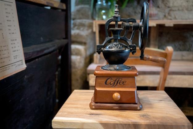 Moedor de café velho vintage em fundo de mesa de madeira