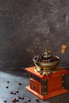 Moedor de café vintage antigo e grãos na textura do fundo da mesa