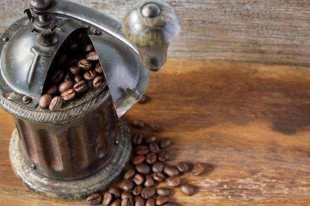 Moedor de café vintage close-up e grãos de café isolados em branco