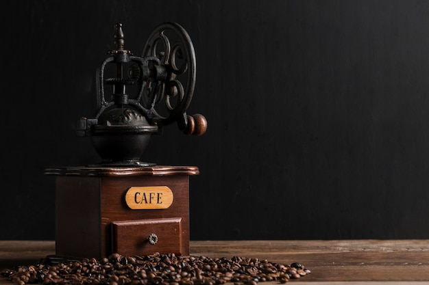 Moedor de café vintage perto de grãos dispersos