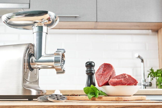 Moedor de carne com carne fresca em uma mesa de madeira no interior da cozinha