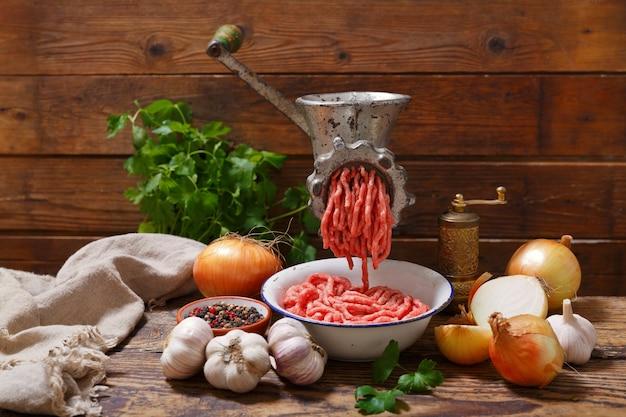 Moedor de carne velha com carne picada e vegetais na mesa de madeira