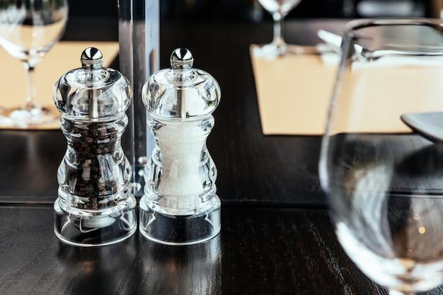 Moedores plásticos claros da pimenta e do sal na tabela de madeira para o tempero do alimento com espaço da cópia.