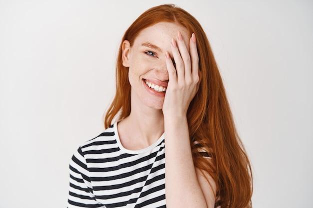 Moel bonita com cabelo ruivo e olhos azuis sorrindo, cobrindo metade do rosto com a mão, em pé sobre uma parede branca