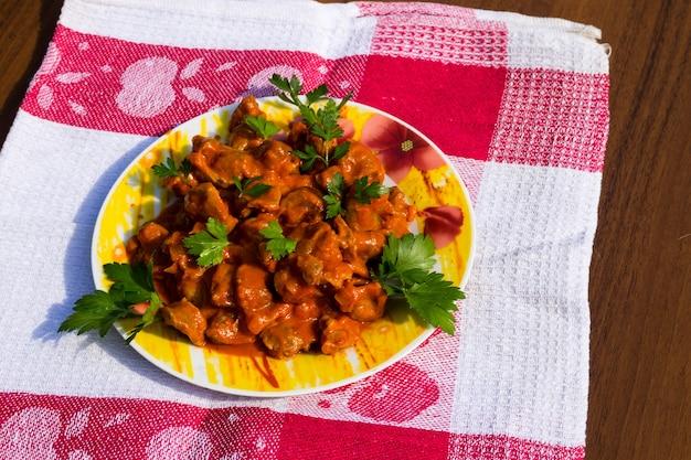 Moela de frango guisada em prato sobre mesa de madeira rústica