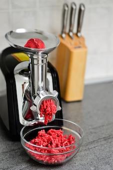Moendo carne vermelha fresca em um moedor de carne manual de metal