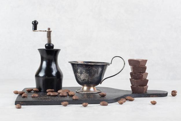 Moer cafeteira, café e grãos no quadro escuro