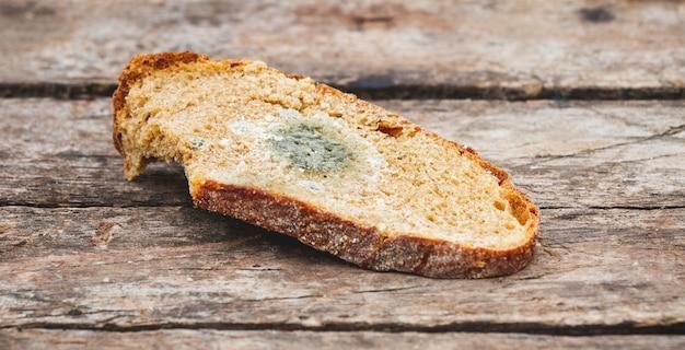 Mofo em uma fatia de pão, deitado sobre uma superfície de madeira. pão dormido, coberto de mofo