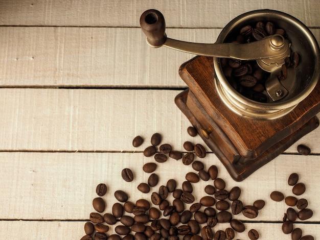 Moinho de moedor de café com grãos de café sobre um fundo claro de madeira.