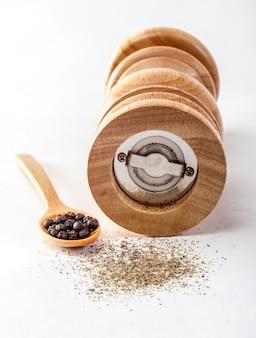 Moinho de pimenta em um fundo branco isolado com pimentos