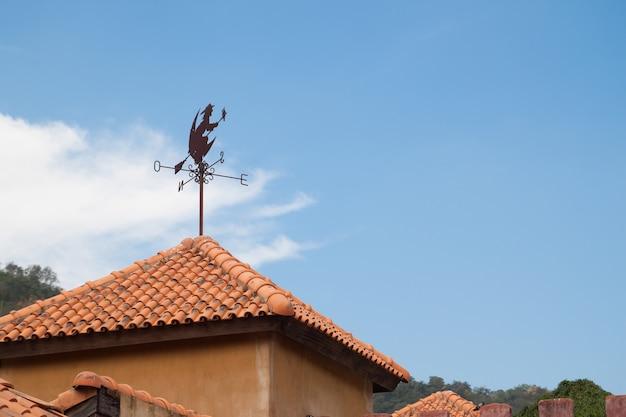 Moinho de vento e bruxa no telhado com céu azul