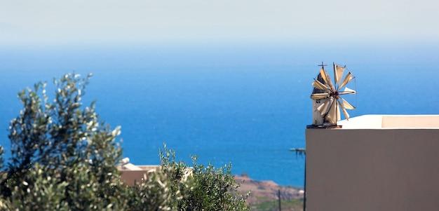 Moinho de vento em miniatura no peitoril de um terraço com vista para o mar