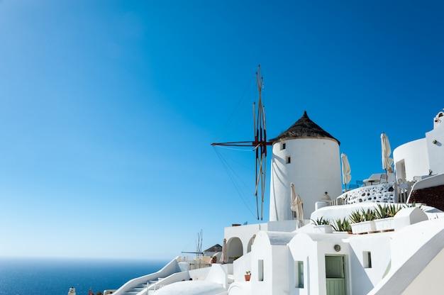 Moinho de vento em oia com céu azul e mar na ilha de santorini