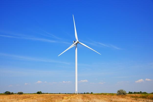 Moinho de vento em um campo contra um céu azul