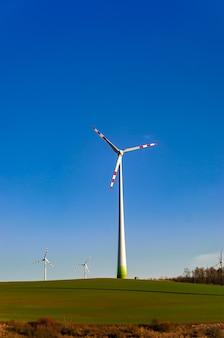 Moinho de vento em um campo verde contra um céu azul. sistemas de extração de recursos naturalmente amigáveis.