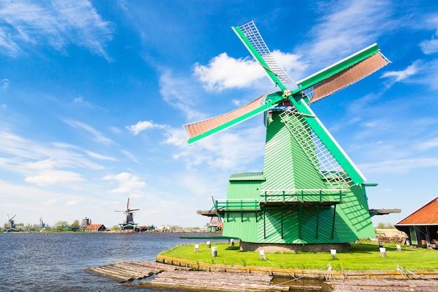 Moinho de vento holandês velho tradicional contra o céu nebuloso azul na vila de zaanse schans, países baixos.