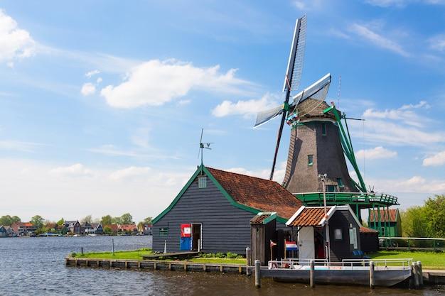 Moinho de vento holandês velho tradicional contra o céu nublado azul na vila de zaanse schans, holanda