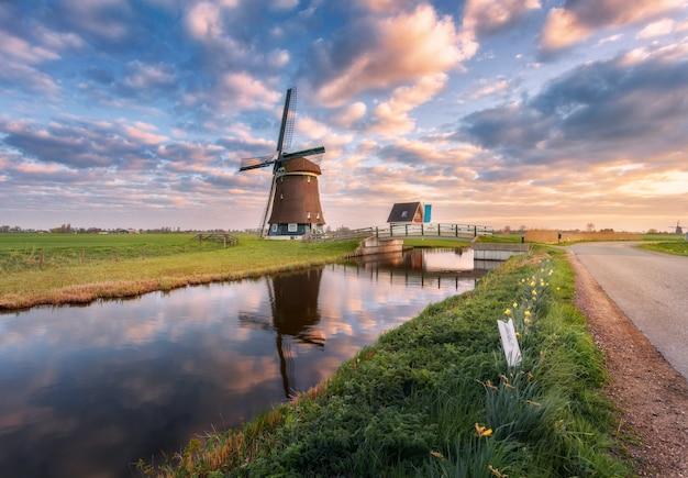 Moinho de vento perto do canal de água ao nascer do sol na holanda